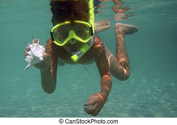 Snorkeling - Young boy swimming underwater and holding...