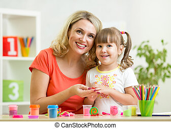 kid girl and mother playing colorful clay toy - happy kid...