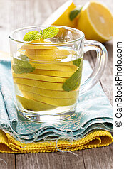 Tea with mint and whole lemon in a transparent cup. Natural...