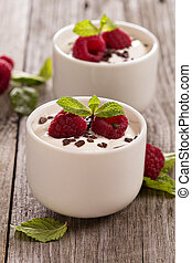 Cream dessert with raspberries in small cups
