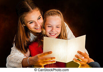 Woman reading Christmas card to youngster. - Close up...