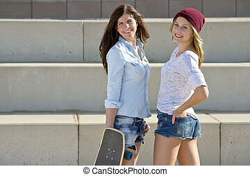 Skater girls - Two cute girls with a skateboard posing for...