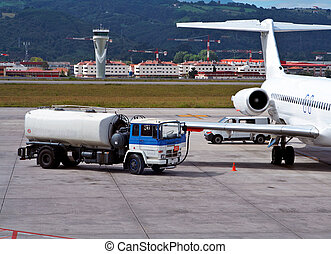 Refueling an airplane - Truck refueling an airplane on the...