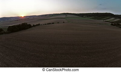 Flight over meadow and fields in sunset aerial shots