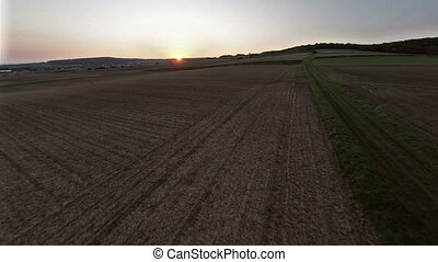 Flight over meadow and fields in sunset aerial shots -...