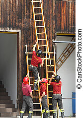 firefighters during the fire drill mount fast wooden ladder