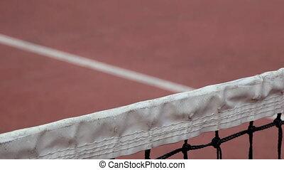 Tennis ball going over the net
