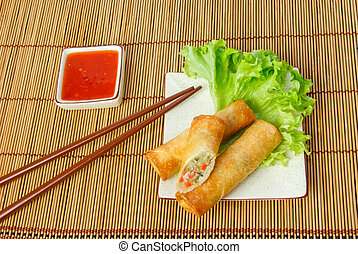 Fried spring rolls, one cut, on a plate with chopsticks...