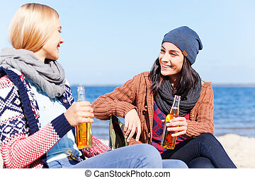 Friendly talk. Two beautiful young women drinking beer and talking to each other while sitting on the beach together