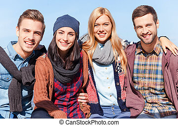 We love spending time together. Four young happy people...