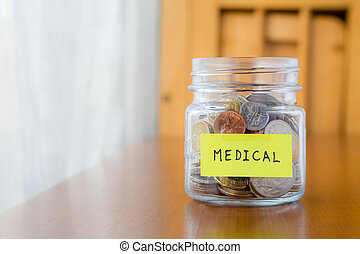 Medical savings plan - Glass bank with many world coins and...