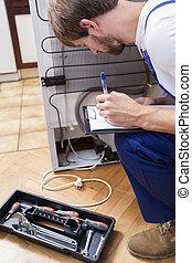 Man working with broken fridge