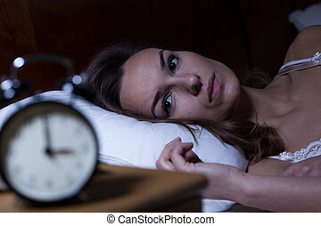 Insomnia - Woman lying in bed suffering from insomnia