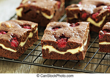 Cheesecake brownies with raspberry on a cooling rack close...