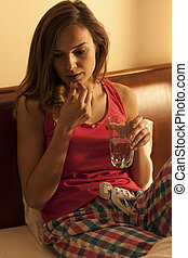 Woman sipping sleeping pills with water - Young woman...
