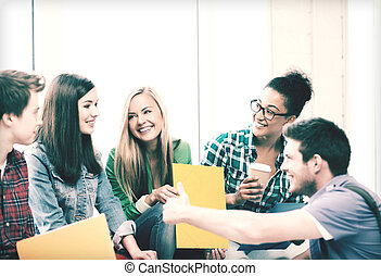 students communicating and laughing at school - education...