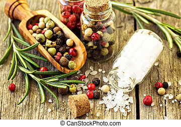 Rosemary, salt and different kinds of pepper on wooden table