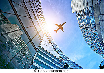 plane over office towers - plane flying over modern glass...