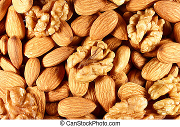 Almonds and walnuts - pile of almond nuts and walnuts as...