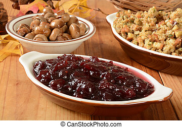 Chunky cranberry sauce on a table with dressing and sauteed...