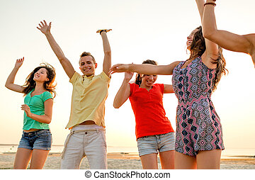 smiling friends dancing on summer beach - friendship, summer...