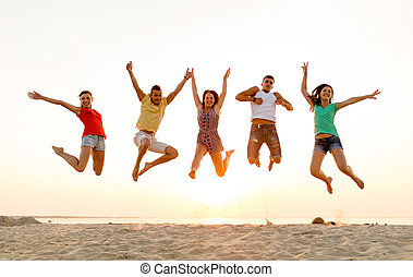 smiling friends dancing and jumping on beach - friendship,...