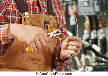 electrician at wiring work - hands of electrician builder...