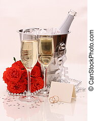 Two champagne glasses, red roses golden wedding rings and...