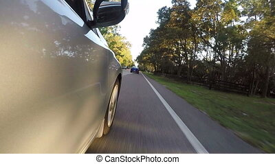 Camera on the outside of car going through a rural area of...