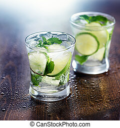 two mojito cocktails on wet wooden table