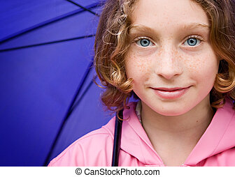 girl holding an umbrella - close up of a pretty 10 year old...