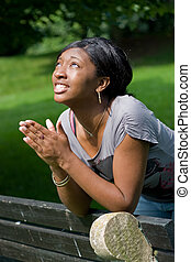 Young Woman Praying - A young woman praying with her hands...
