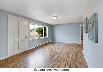 Empty house interior with light blue walls, hardwood floor...