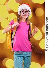 child with Santa Claus red hat, backpack and glasses on bright background