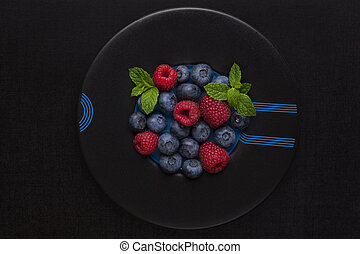 Fresh berries. - Fresh berries on black plate on black...