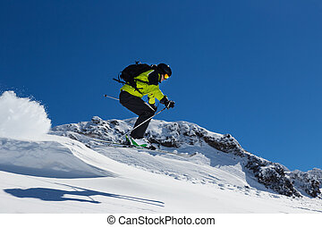 Alpine skier on piste, skiing downhill - Alpine skier skiing...