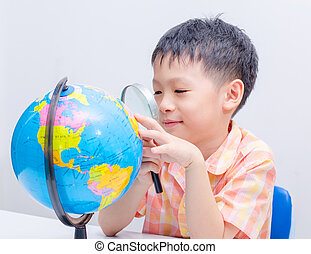 Asian boy looking at a globe by magnifying glass