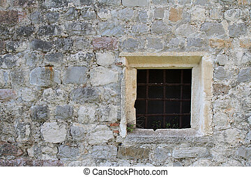 old square window with bars in a stone wall - Small old...