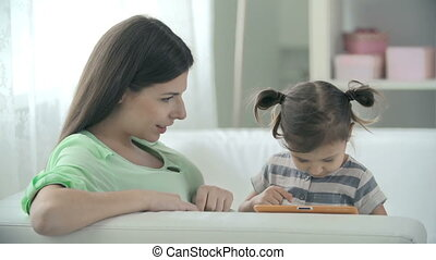 Video Games - Mother and daughter sitting on the sofa and...