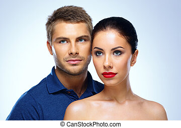 Portrait of a young beautiful couple on blue background