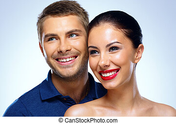 Portrait of a young smiling couple on blue background