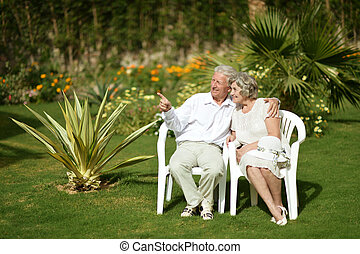 couple sitting on grass - Senior couple sitting on grass at...