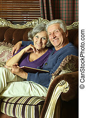 Senior couple on the couch with book