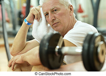 Elderly tired man in a gym with towel