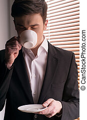 with cup standing near window with jalousie. Young businessman with cup of coffee at morning