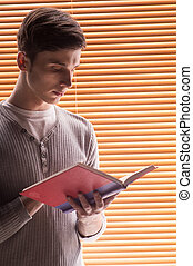 young male student reading book. closeup of man standing near window with jalousie
