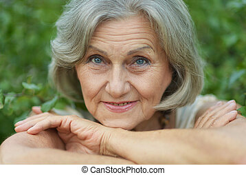 smiling old woman - Nice smiling old woman on the green...