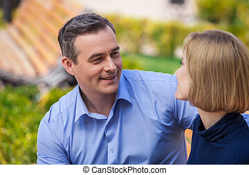 happy couple outside talking and looking at each other. portrait of man and woman having romantic time