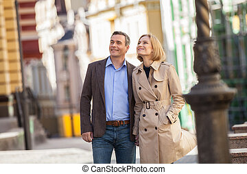 Couple having city break in summer walking on street man...
