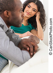 Couple in living room talking while sitting on sofa profile...